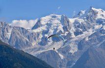 Sportif qui fait du parapente au milieu des montagnes enneigées de Savoie