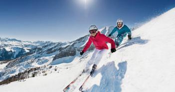 deux skieurs descendent une piste avec vue sur les montagnes derrière eux